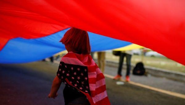 Un bambino con la bandiera degli Stati Uniti corre sotto una bandiera venezuelana dove gli aiuti umanitari per il Venezuela sono immagazzinati a Cucuta, Colombia il 10 febbraio 2019. | Foto: REUTERS/Marco Bello