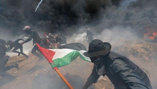 Los manifestantes palestinos corren para protegerse del fuego israelí y los gases lacrimógenos durante una protesta.