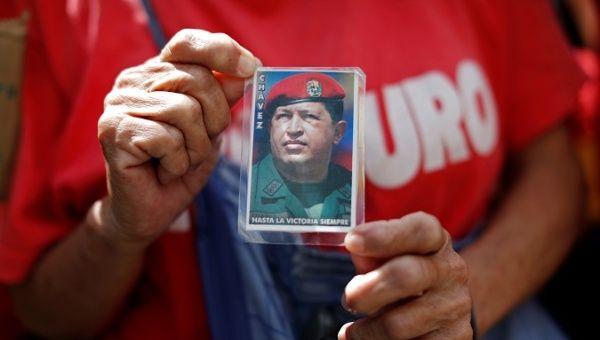 Un partidario del presidente de Venezuela, Nicolás Maduro, tiene una foto del fallecido presidente Hugo Chávez.