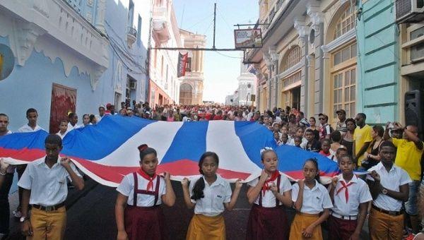 Students hold their country's flag in Santiago de Cuba, Cuba, Nov. 4, 2019.