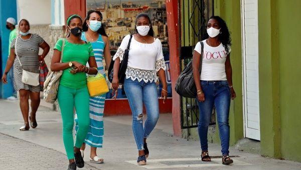 Women walk down a street in Havana, Cuba, Jun. 3, 2021.